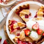 An overhead image of slices of pie with a lattice crust and strawberries and vanilla ice cream