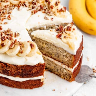 A slice of banana cake with cream cheese frosting being pulled out of whole cake with bananas in the background