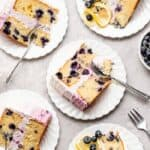 Blueberry lemon layer cake slices on white plates ready to serve with silver forks