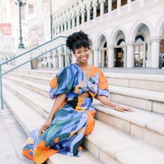 Jocelyn Delk Adams sitting on stairs in front of The Venetian in blue, black and orange dress