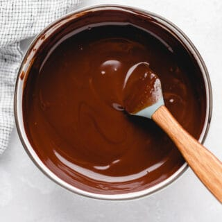 Chocolate ganache being stirred slowly in a white pot with a spatula