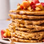 A close up of a large stack of apple cinnamon pancakes with syrup dripping down the sides
