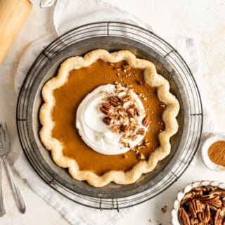 A classic pumpkin pie baked with whipped cream and pecans against a white background with a rolling pin next to it