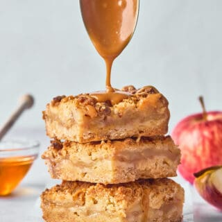 Honey caramel sauce dripping down over a stack of apple crumble bars against a gray background